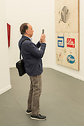 "A man takes a photo of art in the galery of the Peres Projects. On the wall is a diptych titled ""APA Diptych"" by Mark Flood."