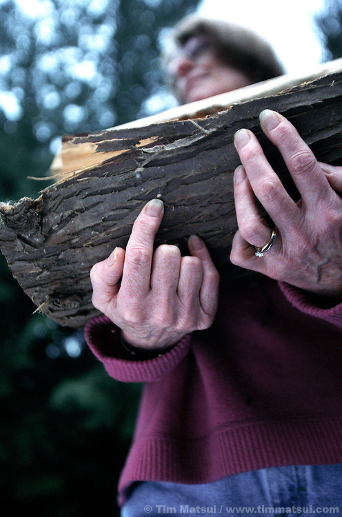 A mature caucasian woman carries firewood.