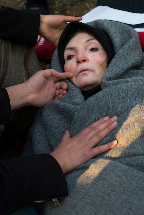 A woman in shock is cared for by other refugees and volunteers after arriving on Lesbos Island on March 20, 2016 near Mitilini, Greece.