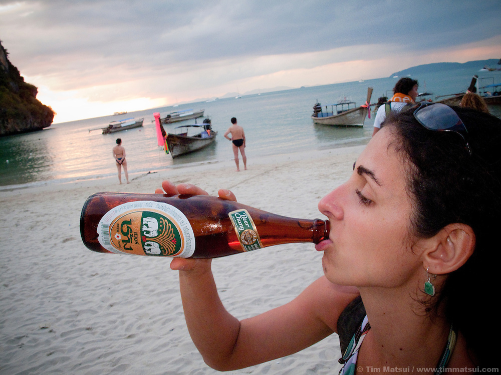 A woman drinks a local Thai beer on the beach in Raileh, Thailand.