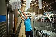 11 JULY 2011 - BANGKOK, THAILAND:    An employee of the State Railways of Thailand throws bedding onto an overnight train bound for Chiang Mai in Hua Lamphong station in Bangkok. Hua Lamphong Grand Central Railway Station, officially known as the Bangkok Grand Central Terminal Railway Station, is the main railway station in Bangkok, Thailand. It is located in the center of the city in Pathum Wan District, and is operated by the State Railway of Thailand. The station was opened on 25 June 1916, after six years' construction. The station was built in an Italian Neo-Renaissance style, with decorated wooden roofs and stained glass windows. The architecture is attributed to Turin-born Mario Tamagno, who, with countryman Annibale Rigotti made a mark on early 20th century public building in Bangkok. The pair also designed Bang Khun Prom Palace (1906), Ananda Samakhom Throne Hall in The Royal Plaza (1907-15) and Suan Kularb Residential Hall and Throne Hall in Dusit Garden, among other buildings..There are 14 platforms and 26 ticket booths. Hua Lamphong serves over 130 trains and approximately 60,000 passengers each day. Thailand has the most advanced rail system in Southeast Asia and trains from Hua Lamphong serve all corners of the Kingdom.     PHOTO BY JACK KURTZ