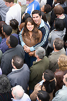 Young couple embracing among crowd