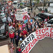Amsterdam, 21-09-2013.  Vanuit 16 steden in het land kwamen bussen naar Amsterdam met betogers die meededen aan de demonstratie tegen de geplande bezuinigingen van het kabinet. De organisatie Comité Stop Bezuinigingen schatte de opkomst op ongeveer 5000 mensen. De manifestatie begon op het Beursplein. Vandaar trokken de demonstranten naar het beeld van de Dokwerker op het Jonas Daniël Meijerplein. Daar werd gesproken door onder andere SP-leider Emile Roemer en Henk Krol (50Plus). Meer dan 50 maatschappelijke organisaties hebben hun steun toegezegd aan de protestactie. Onder meer de Amsterdamse afdelingen van FNV Bondgenoten, Abvakabo FNV en SP en GroenLinks namen het initiatief tot de demonstratie. Zij menen dat de bevolking ,,het niet langer pikt'' dat de regering weer miljarden wil bezuinigen op onder meer zorg en kinderopvang. Volgens het comité worden de kosten van de crisis afgewenteld op kwetsbare groepen in de samenleving en worden ,,bonussen, belastingontwijking en de topinkomens nauwelijks aangepakt''. Foto: Tussen de betogers/demonstranten lopen vooraan Emile Roemer en Henk Krol.