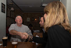 Ardent Brexiteer construction worker Philip Davenport, 63, shakes hands with Samantha Dark as they debate  Brexit with Bild Reporter Philip Fabian ay the Whippet In in Kensal Rise, North West London. London January 13 2019.