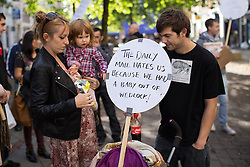"""© Licensed to London News Pictures . 06/10/2013 . Manchester , UK . A man , woman and child with a placard that reads """" The Daily Mail hates us because we had a baby out of wedlock """" . A demonstration against the Daily Mail newspaper in central Manchester's St Anne's Square today (6th October 2013) . Photo credit : Joel Goodman/LNP"""