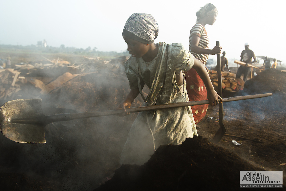 A girl uses a shovel to remove dirt covering burning charcoal at a wood charcoal production site on the outskirts of San Pedro, Bas-Sassandra region, Côte d'Ivoire on Sunday March 4, 2012. Men, women and children - who don't go to school - work here seven days a week.