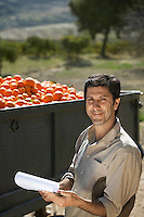 Portrait of farmer standing by truck with oranges