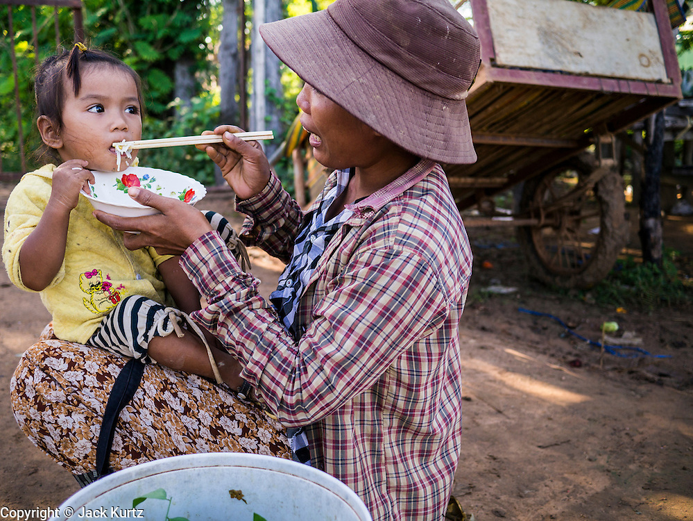 29 JUNE 2013 - BATTAMBANG, CAMBODIA:  A woman helps her daughter eat a bowl of noodles along side the bamboo train tracks. The bamboo train, called a norry (nori) in Khmer is a 3m-long wood frame, covered lengthwise with slats made of ultra-light bamboo, that rests on two barbell-like bogies, the aft one connected by fan belts to a 6HP gasoline engine. The train runs on tracks originally laid by the French when Cambodia was a French colony. Years of war and neglect have made the tracks unsafe for regular trains.  Cambodians put 10 or 15 people on each one or up to three tonnes of rice and supplies. They cruise at about 15km/h. The Bamboo Train is very popular with tourists and now most of the trains around Battambang will only take tourists, who will pay a lot more than Cambodians can, to ride the train.       PHOTO BY JACK KURTZ