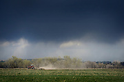 Dark clouds are seen overhead as a man in a tractor plows a field near Airport Road and Rogers Road in Longmont on Wednesday.<br /> Matthew Jonas/Staff Photographer April 13, 2016