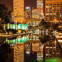 Indianapolis skyline at night with reflection of downtown city buildings on the Indiana Central Canal. The canal was built in the 1800s and serves as a recreational attraction along Canal Walk.
