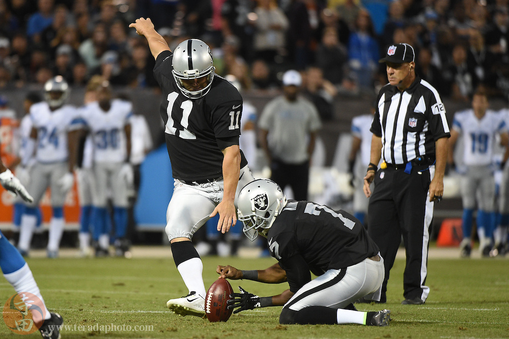 August 15, 2014; Oakland, CA, USA; Oakland Raiders kicker Sebastian Janikowski (11) kicks out of the hold by punter Marquette King (7) for an extra point during the second quarter against the Detroit Lions at O.co Coliseum.