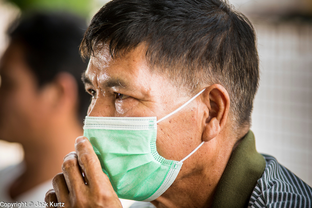 "09 APRIL, 2013 - DO SAKET, CHIANG MAI, THAILAND:  A man wearing a breathing filter waits to see a doctor in Doi Saket, Chiang Mai province, Thailand. He said he was wearing the mask and waiting to see the doctor because he was having a hard time breathing because of the smoke in the air.  The ""burning season,"" which roughly goes from late February to late April, is when farmers in northern Thailand burn the dead grass and last year's stubble out of their fields. The burning creates clouds of smoke that causes breathing problems, reduces visibility and contributes to global warming. The Thai government has banned the burning and is making an effort to control it, but the farmers think it replenishes their soil (they use the ash as fertilizer) and it's cheaper than ploughing the weeds under.     PHOTO BY JACK KURTZ"