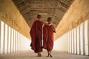 Buddhist monks walking down covered pathway, Bagan, Myanmar