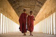 Buddhist monks walking down covered pathway, Bagan, Myanmar