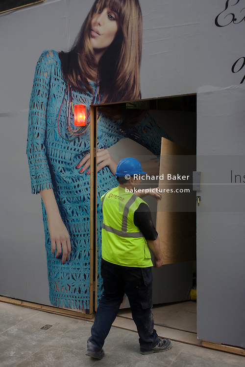 Workman carries plyboard materials on to site below fashion girl hoarding.