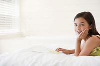Girl reading story book lying on stomach on bed head and shoulders