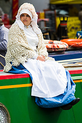 Little Venice, London, April 30th 2017. Narrowboaters from all over the uK gather for the annual Canalway Cavalcade, held on the May Day Bank holiday weekend, organised by the Inland Waterways Association, where boaters get the chance to display their immaculately prepared and brightly painted craft as well as compete in various manoeuvring tests. PICTURED: A girl in traditional dress sits on the roof of her narrowboat as it glides along the canal.<br /> Credit: &copy;Paul Davey<br /> To licence contact: <br /> Mobile: +44 (0) 7966 016 296<br /> Email: paul@pauldaveycreative.co.uk<br /> Twitter: @pauldaveycreate