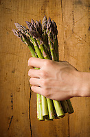 Studio still lifes of a hand gripping a bunch of asparagus in front of a wood background.