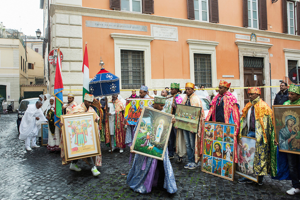 ROME, ITALY - 23 NOVEMBER 2014: Eritrean refugees of the Orthodox Tewahedo Church hold framed religious icons as they stand in fron of the church of St-Michael to celebrate St-Michael in Rome, Italy, on November 23th 2014.