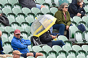 A spectator has an umbrela up as spots of rain are in the air during the Specsavers County Champ Div 1 match between Somerset County Cricket Club and Essex County Cricket Club at the Cooper Associates County Ground, Taunton, United Kingdom on 23 September 2019.