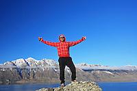 Backpacker in red jacket enjoying views of Lake Hawea Wanaka South Island New Zealand in winter