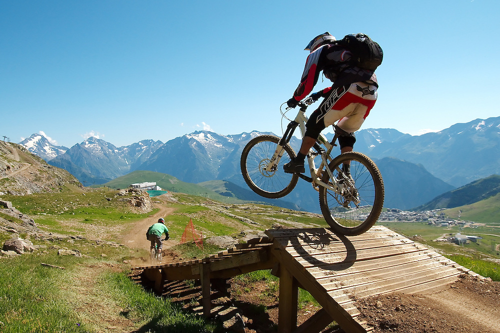 An unknown mountain biker jumps off a ramp with the French alps in the background, during the 2008 MegaAvalanche downhill MTB race, held at Alpe d'Huez in Southern France. The MegaAvalanche race is the longest downhill mountain biking race in the world, taking place every summer in France. In this year's race (2008) the weather closed in and stopped competitors racing over the full course. As a result, the event was started lower down over a shorter course, and won with a fantastic performance by Rene Wildhaber.