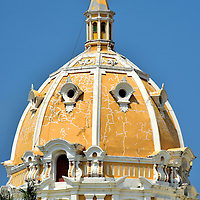 Dome of Iglesia de San Pedro Claver in Old Town, Cartagena, Colombia<br /> The dome of the Church of San Pedro Claver is a prominent landmark in the skyline of El Centro, the historic district of Cartagena. The paint is peeling and it shows signs of disrepair. Perhaps this gorgeous yet humble façade is a fitting tribute to San Pedro Claver. This Jesuit priest spent 40 years of his life greeting, caring for and baptizing over 300,000 African slaves as they entered Cartagena's port until he died in 1654.
