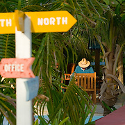 Man at rest in early morning light with signpost in foreground,Journey's End Resort, Ambergris Caye, Belize