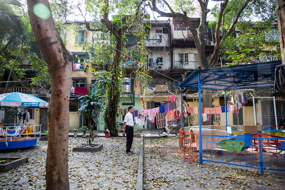 Vietnamese man stands in a playground of a social housing compound, Hanoi, Vietnam, Southeast Asia