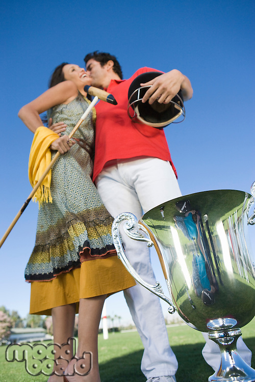 Couple kissing by polo trophy