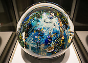 "Megaplanet, a 100-pound sphere paperweight, was made in 2006 of fused murrine, furnace-worked, applied cane drawing, applied decoration, applied gold and silver foils, by Josh Simpson (American born 1949), the culmination of 30+ years of experience. The fascinating Corning Museum of Glass (CMOG.org) covers the art, history and science of glass, brought to life through live glassmaking demonstrations, offered all day, every day, in Corning, New York, USA. The not-for-profit museum was founded in 1951 by Corning Glass Works (now Corning Incorporated) and has a collection of more than 45,000 glass objects, some over 3500 years old, the ""world's best collection of art and historical glass."""