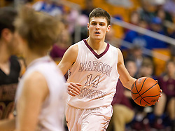 Wheeling Central guard Chase Harler (14) dribbles the ball at the top of the key against Williamstown during a semi-final game at the Charleston Civic Center.