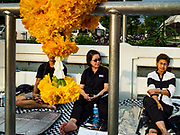 24 OCTOBER 2017 - BANGKOK, THAILAND: Women framed by a marigold garland on Atsadang Road wait to enter the royal cremation site. People started camping out along Atsadang Road in Bangkok near the royal cremation site on Monday. The gates won't open until Wednesday morning and the cremation isn't until Thursday night, so most people will sleep outside, on sidewalks and footpaths for three nights. Hundreds of thousands of people are expected to try to get into Sanam Luang, the site of the cremation of Bhumibol Adulyadej, the Late King of Thailand, but the site will only hold about 60,000 people. The Thai government has built replica crematoriums around Bangkok to accommodate the overflow crowds.        PHOTO BY JACK KURTZ