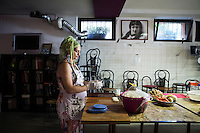 """ROME, ITALY - 3 JULY 2016: Gipsy Queens member Codruta Balteau (24) shapes pita dough for the the a food stand at the iFest, an alternative music festival, here in the Astra 19 social center in Rome, Italy, on July 3rd 2016.<br /> <br /> The Gipsy Queens are a travelling catering business founded by Roma women in Rome.<br /> <br /> In 2015 Arci Solidarietà, an independent association for the promotion of social development, launched the """"Tavolo delle donne rom"""" (Round table of Roma women) to both incentivise the process of integration of Roma in the city of Rome and to strengthen the Roma women's self-esteem in the context of a culture tied to patriarchal models. The """"Gipsy Queens"""" project was founded by ten Roma women in July 2015 after an event organised together with Arci Solidarietà in the Candoni Roma camp in the Magliana, a neighbourhood in the South-West periphery of Rome, during which people were invited to dance and eat Roma cuisine. The goal of the Gipsy Queen travelling catering business is to support equal opportunities and female entrepreneurship among Roma women, who are often relegated to the roles of wives and mothers."""