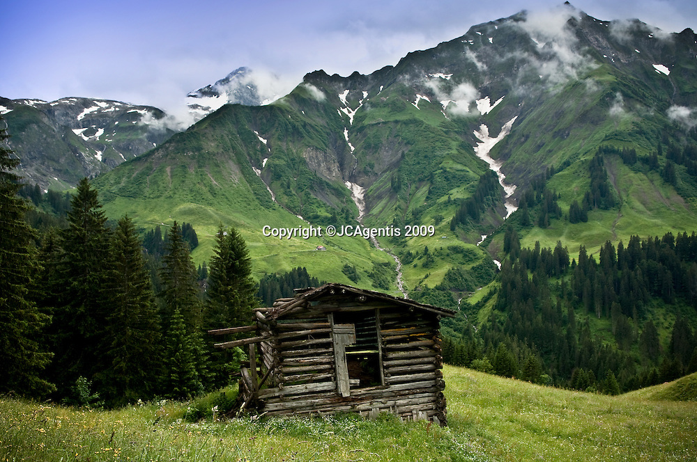 Gorgeous austrian landscape at the foothills of the Alp Mountains in summer with historic cabins adorning the countryside