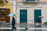 SANTA MARIA DI CASTELLABATE (CASTELLABATE), ITALY - 14 FEBRUARY 2018: Men walk in the main street of Santa Maria di Castellabate, the town home to Alessia d'Alessandro (28), the Five Stars Movement (M5S, Movimento 5 Stelle) candidate running for the Chamber of Deptuies in the 2018 Italian General Elections, in Santa Maria di Castellabate (Castellabate), Italy, on February 14th 2018.<br /> <br /> Santa Marina di Castellabate is part of the electoral college of Agropoli, in the Campania region (southern Italy) in which Franco Alfieri (Democratic Party, PD, Partito Democratico), politically active for the past 30 years, is running agains the 28-years old Alessia d'Alessandro (Five Stars Movement, M5S, Movimento 5 Stelle).<br /> <br /> The 2018 Italian general election is due to be held on 4 March 2018 after the Italian Parliament was dissolved by President Sergio Mattarella on 28 December 2017.<br /> Voters will elect the 630 members of the Chamber of Deputies and the 315 elective members of the Senate of the Republic for the 18th legislature of the Republic of Italy, since 1948.Santa<br /> <br /> The 2018 Italian general election is due to be held on 4 March 2018 after the Italian Parliament was dissolved by President Sergio Mattarella on 28 December 2017.<br /> Voters will elect the 630 members of the Chamber of Deputies and the 315 elective members of the Senate of the Republic for the 18th legislature of the Republic of Italy, since 1948.