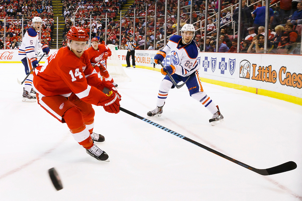Mar 9, 2015; Detroit, MI, USA; Edmonton Oilers defenseman Jordan Oesterle (82) passes the puck past Detroit Red Wings center Gustav Nyquist (14) in the third period at Joe Louis Arena. Detroit won 5-2. Mandatory Credit: Rick Osentoski-USA TODAY Sports