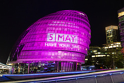 © Licensed to London News Pictures. 04/062016. LONDON, UK.  City Hall is illuminated in hot pink, with a '5 May' calendar projection to mark the London Mayoral and local elections taking place on 5th May and remind Londoners to visit their polling stations and vote. City Hall is one of a number of landmarks across London that are being illuminated in hot pink this evening.  Photo credit: Vickie Flores/LNP
