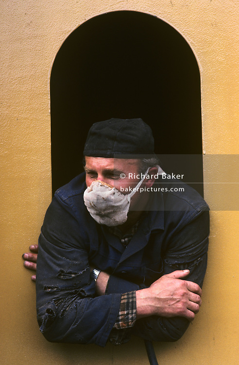 A shipbuilder wearing a face mask, leans through the incomplete window belonging to the superstructure of a large German ferry at the Polish Gdansk shipyard - once known as the Lenin Shipyard but still the largest of its kind in modern Poland. The grimy and hazardous working conditions make for a dangerous environment in which to work. His overalls are torn from jagged steel edges and his skin is dirty. Here in 1980 the union Solidarity (Solidarnosc) was conceived and was partly responsible for a growing dissent against Communist rule, ultimately contributing towards the fall of the Berlin Wall. Lech Walesa started his political career as an electrical technician here, going on to lead Solidarity and then to become President of a democratic Poland. Today the city of Gdansk is a major industrial city and shipping port.