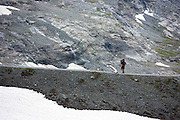 Hiker with camping gear on the Eiger Trail by Eiger Glacier, Eigergletscher, in Swiss Alps, Bernese Oberland, Switzerland