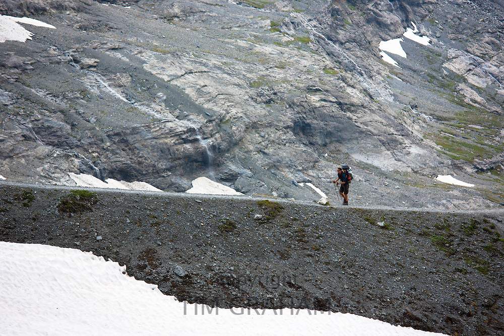 Hiker with camping gear on the Eiger Trail by Eiger Glacier, Eigergletscher, in Swiss Alps, Bernese Oberland, Switzerland