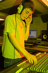 Teenaged DJ using mixing desk to make music,