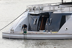 © Licensed to London News Pictures. 24/10/2018. London, UK.  Crew staff wash the 308 feet long luxury superyacht Kismet, reportedly owned by Pakistani-American billionaire, Shahid Khan, that has arrived in London and moored at Butlers Wharf on the River Thames near Tower Bridge. Mr Khan owns the National Football League (NFL) team, the Jacksonville Jaguars, who are due to play the Philadelphia Eagles in an International Series game at Wembley on Sunday 28th October. Kismet has 6 staterooms, with the master bedroom having its own private deck with jacuzzi and helipad.  Photo credit: Vickie Flores/LNP