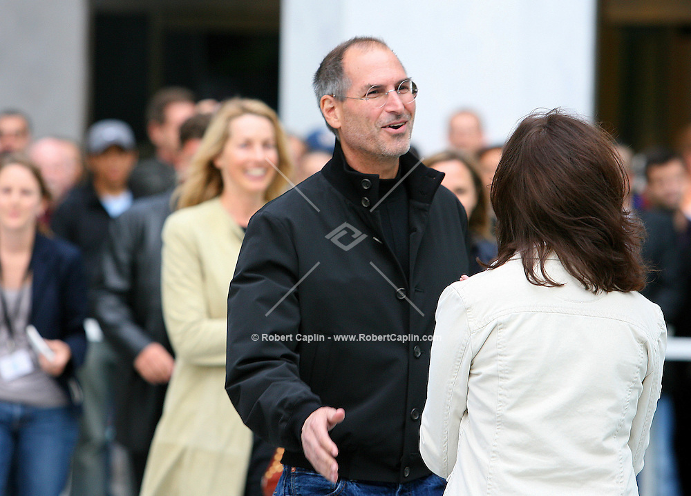 Steve Jobs, Apple Computer, Inc. chief executive officer, in black, arrives outside the new Apple Store in New York moments prior to the grand opening on Friday, May 19, 2006. Apple Computer Inc., maker of the iPod music player, opened a 24-hour subterranean store in New York City, marking five years in retailing with an outlet built beneath a 32-foot glass cube.
