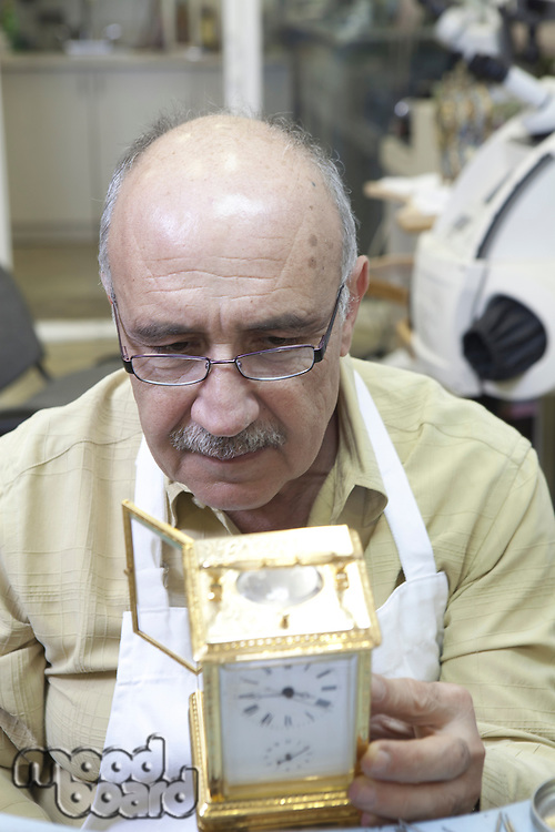 Close-up of a mature man concentrating on repairing clock in workshop