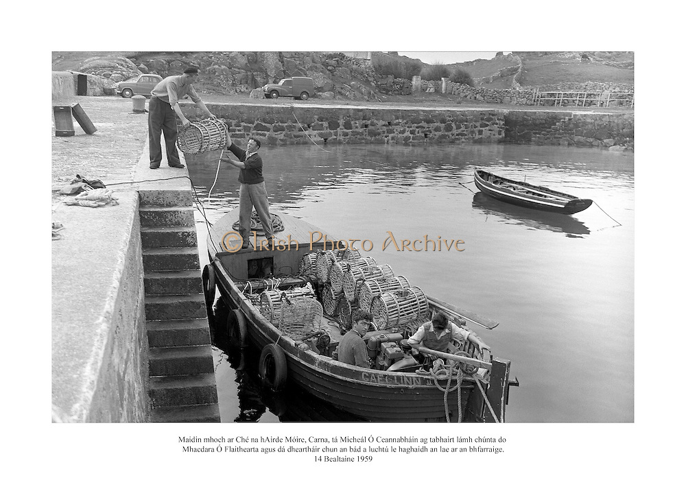 14 Bealtaine 1959<br /> Maidin mhoch ar Ché na hAirde Móire, Carna, tá Micheál Ó Ceannabháin ag tabhairt lámh chúnta do Mhacdara Ó Flaithearta agus dá dheartháir chun an bád a luchtú le haghaidh an lae ar an bhfarraige.<br /> <br /> Early morning on the quayside at Ard Mhoir, Carna, as Micheal O Canabhain helps his neighbours Mac Dar O'Fleartaigh and his brother to load their fishing boat for the days trip.