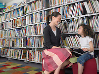 Woman and girl holding book sitting in library