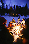 Winter campfire at dusk in the mountains of Idaho with a group of hikers warming themselves as a winter cabin glows warm in the background