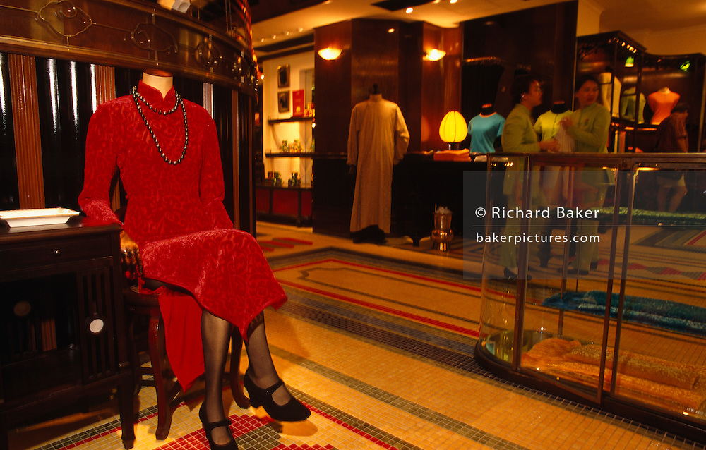 "On the very last day of British rule over its Hong Kong colony, we see an elegant but headless life-size clothing mannequin seated on a chair on the shop floor of Chinese clothing brand Shanghai Tang. In the brand's flagship store, the last hours tick away before the transfer of sovereignty of Hong Kong from the United Kingdom to the Peoples Republic of China (PRC), often referred to as ""The Handover"" on June 30, 1997. Midnight of that day signified the end of British rule and the transfer of legal and financial authority back to China. Shanghai Tang is an international clothing chain company, founded in 1994 by Hong Kong businessman David Tang Wing Cheung. This was the original store in Hong Kong's Pedder Street (in Central) providing the lead for 24 outlets worldwide."