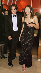 Actor HUGH GRANT and model LIZ HURLEY, at a party in London on 22nd February 1999.MON 134